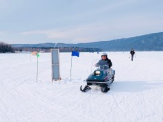 Driving a snowmobile around frozen Lake Akan