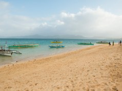 Boats dock in by the long stretch of beach. Photo by Ram Cambiado