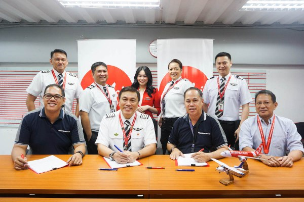 Philippines AirAsia Inc. and Omni Aviation Corporation sign partnership for the Cadet Pilot Program on Wednesday, July 24. Standing L-R: Capt. Christopher Natividad, Chief Pilot for Flight Safety; FO Nicholas Serrano, Quality Assurance Manager; AirAsia Cabin Crew; Capt. Jasmine Timola and FO Bruce Melvin Tan, Line Pilots. Seated L-R: Capt. Eleazar Cayago, Omni Aviations Head of Training; Capt. Dexter Comendador, Philippines AirAsia CEO; Mr. Steven Virata, Omni Aviations COO; Capt. Nilo Oropesa, Chief Pilot for Operations.