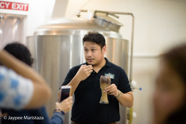 Mr. James telling us how he creates craft beer. He's holding a glass of malt, one of the main ingredients in making beers. © Jaypee Maristaza