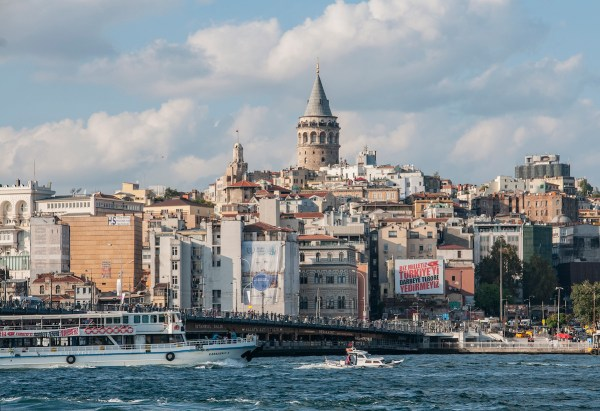The view of the Golden Horn from the ferry dock near the crowded Galata Bridge with the medieval cylindrical stone Galata Tower in the distance built by the Genoese in 1348.