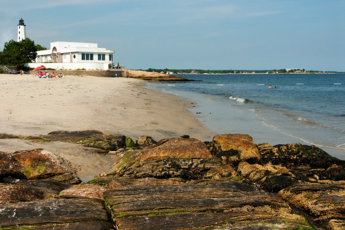 Beach Surrounds Lighthouse in Connecticut photo via Depositphotos