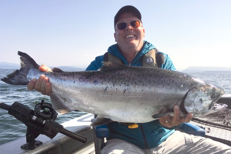 Smiling man holds large chinook salmon