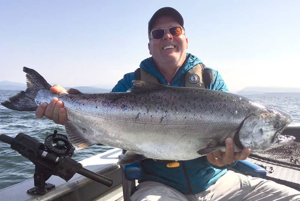 Smiling man in hat with large chinook salmon