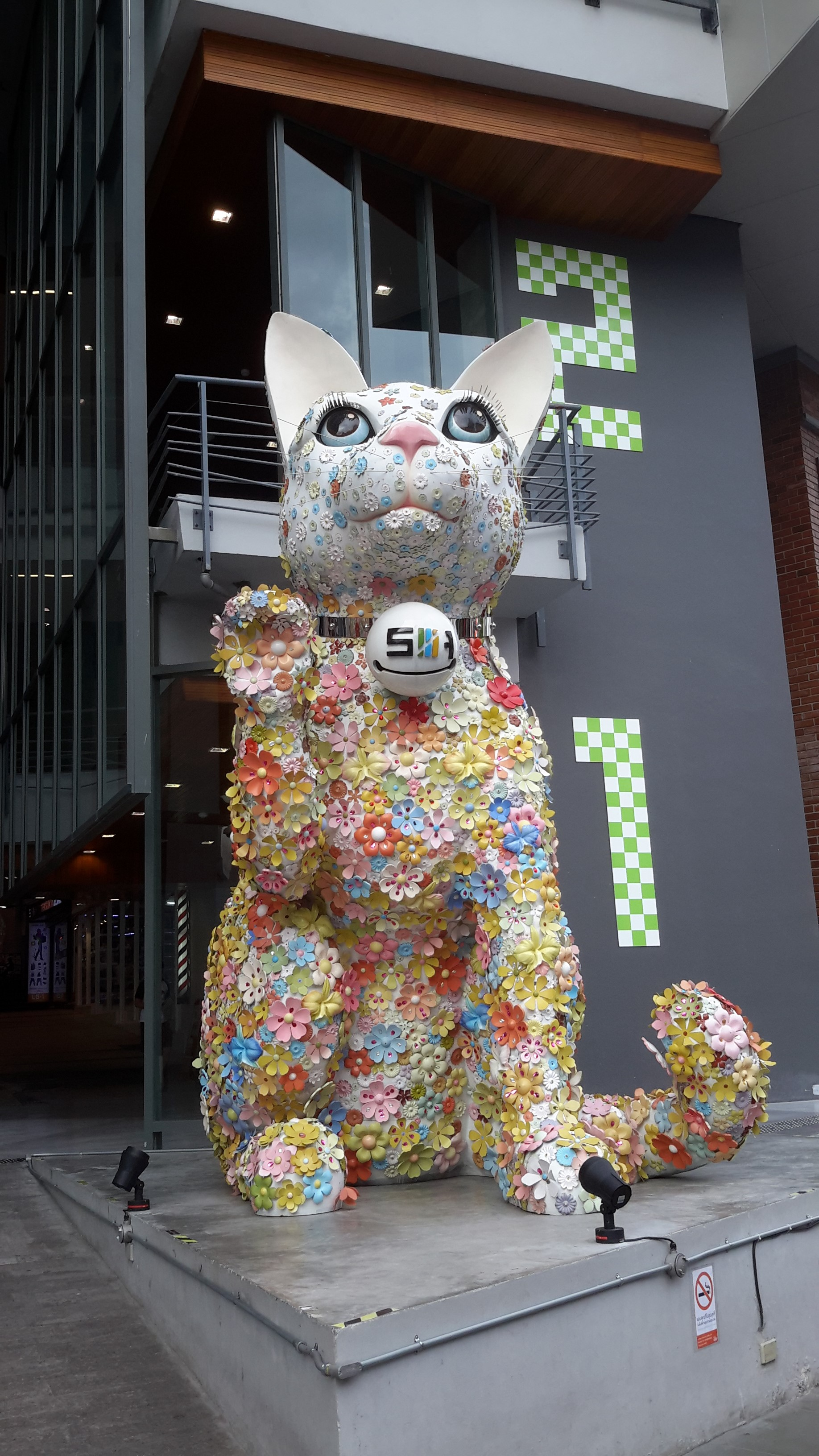 GIANT LUCKY CAT BECKONS YOU TO THE MALL .