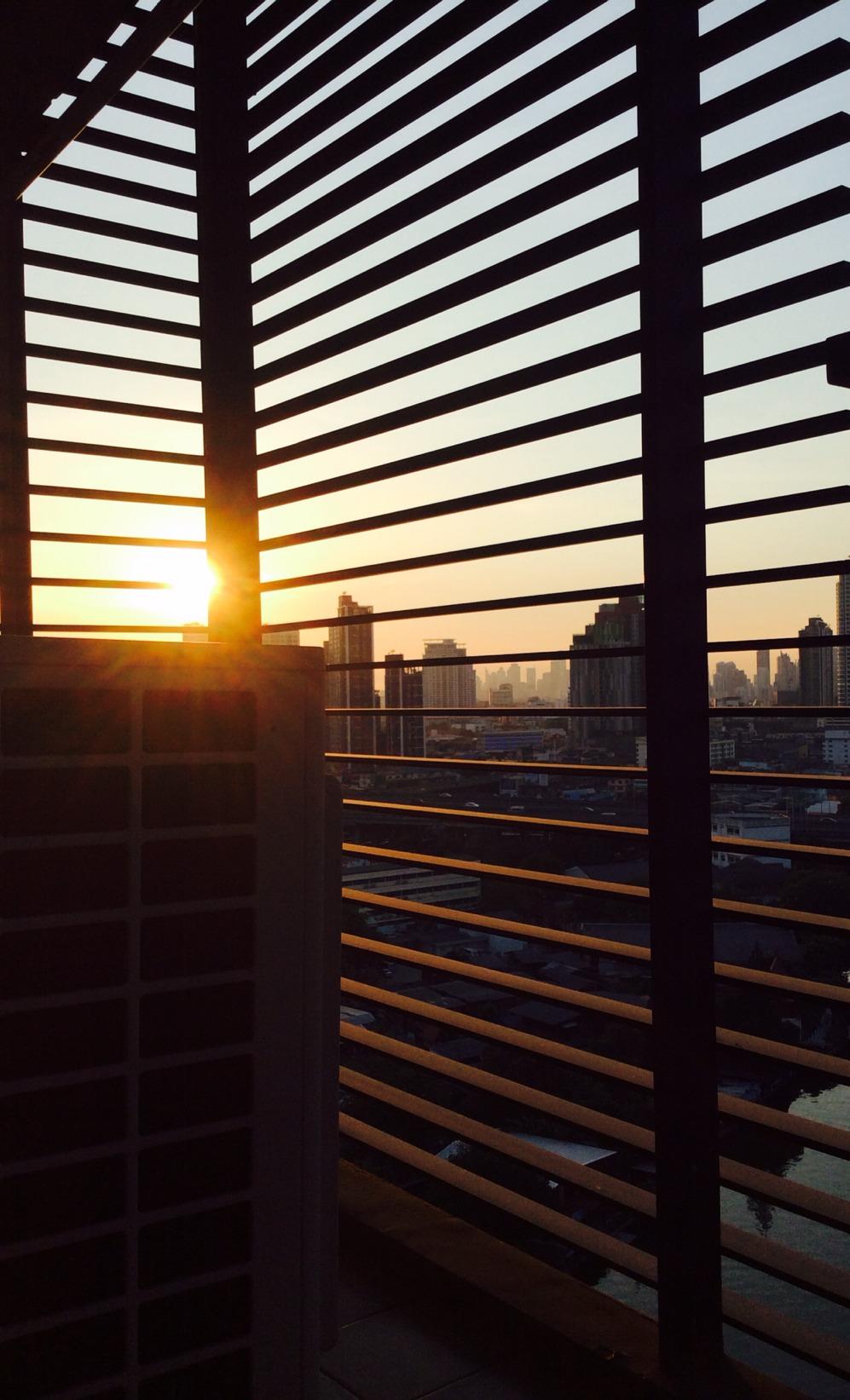 Sunset through silhouette barred-balcony.