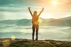 Strong Resilient Woman standing on the horizon with her arms up in triumph. Managing Mental Health During COVID   Online therapy in California mental health services with Outside the Norm Counseling in Temecula, CA