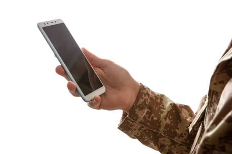 Arm of a soldier holding a phone for online therapy in California, private and secure telehealth services in Temecula, CA. Outside the Norm Counseling can help you get mental health support from an online counselor in California today!