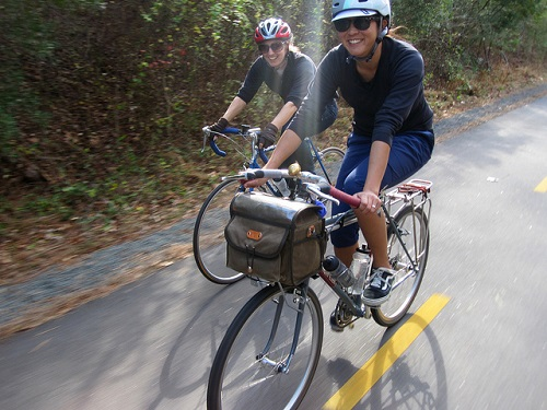 Two people bike commuting with bags on their bikes.