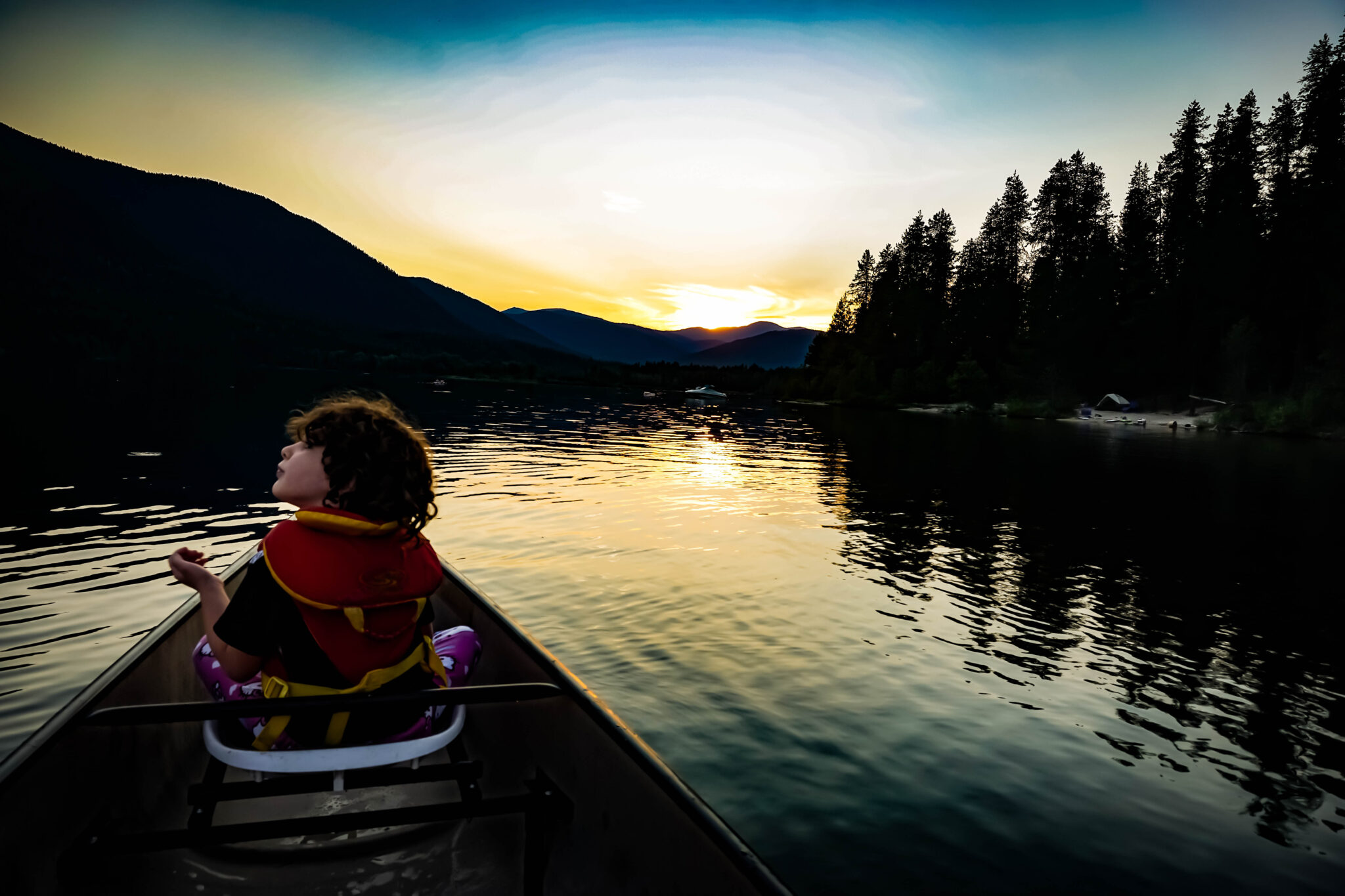 Girl in a canoe at sunset on Priest Lake.