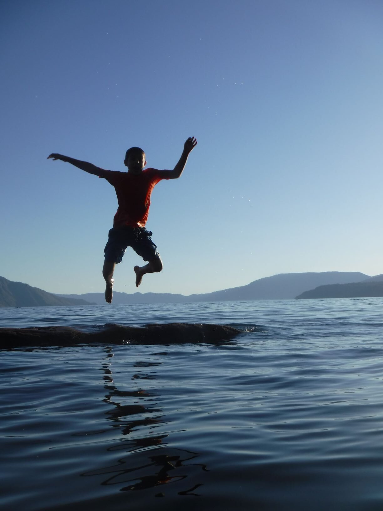 A boy jumping off a log floating in Lake Pend Oreille, with a view of hills in the far background.