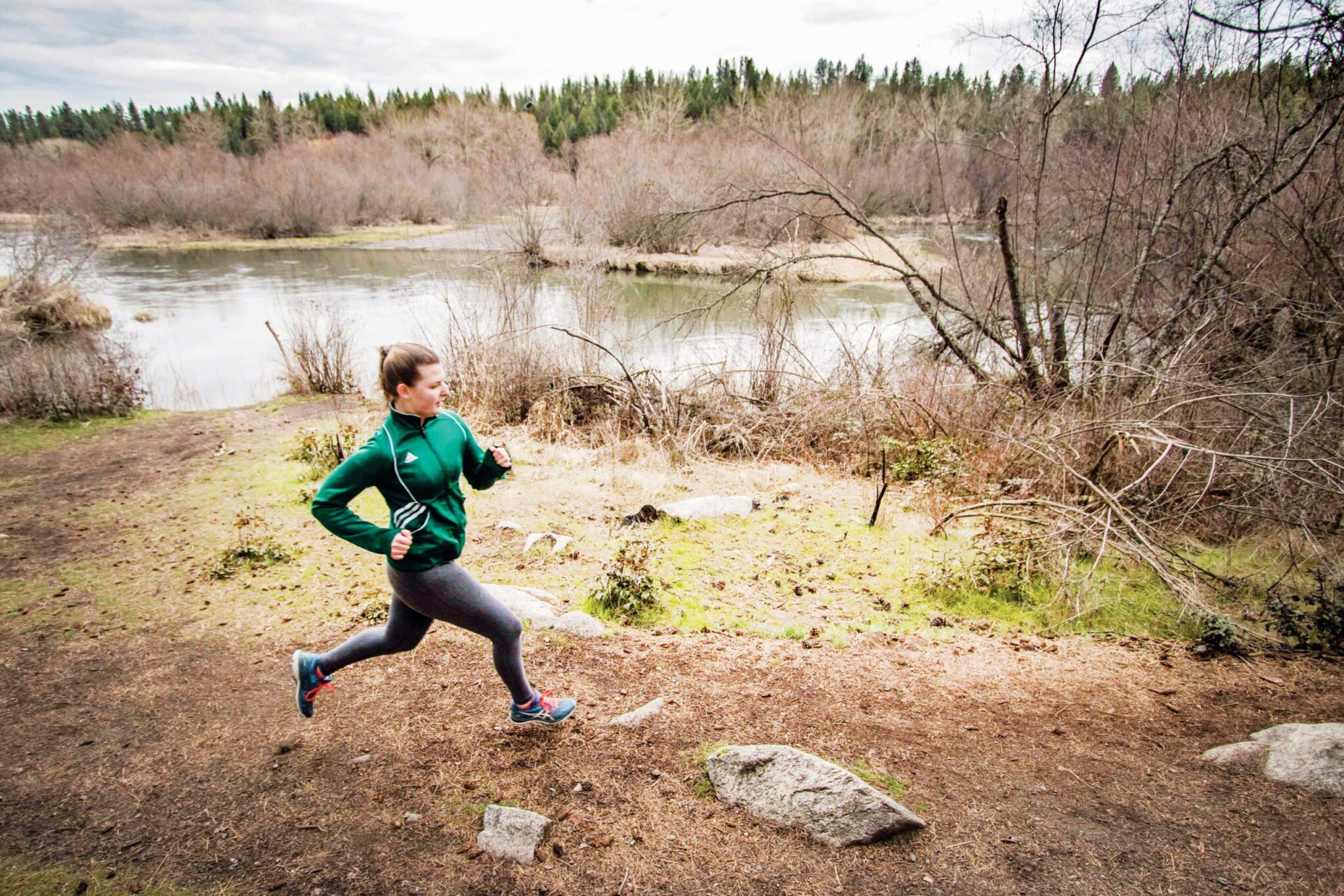 A woman running along a river trail.