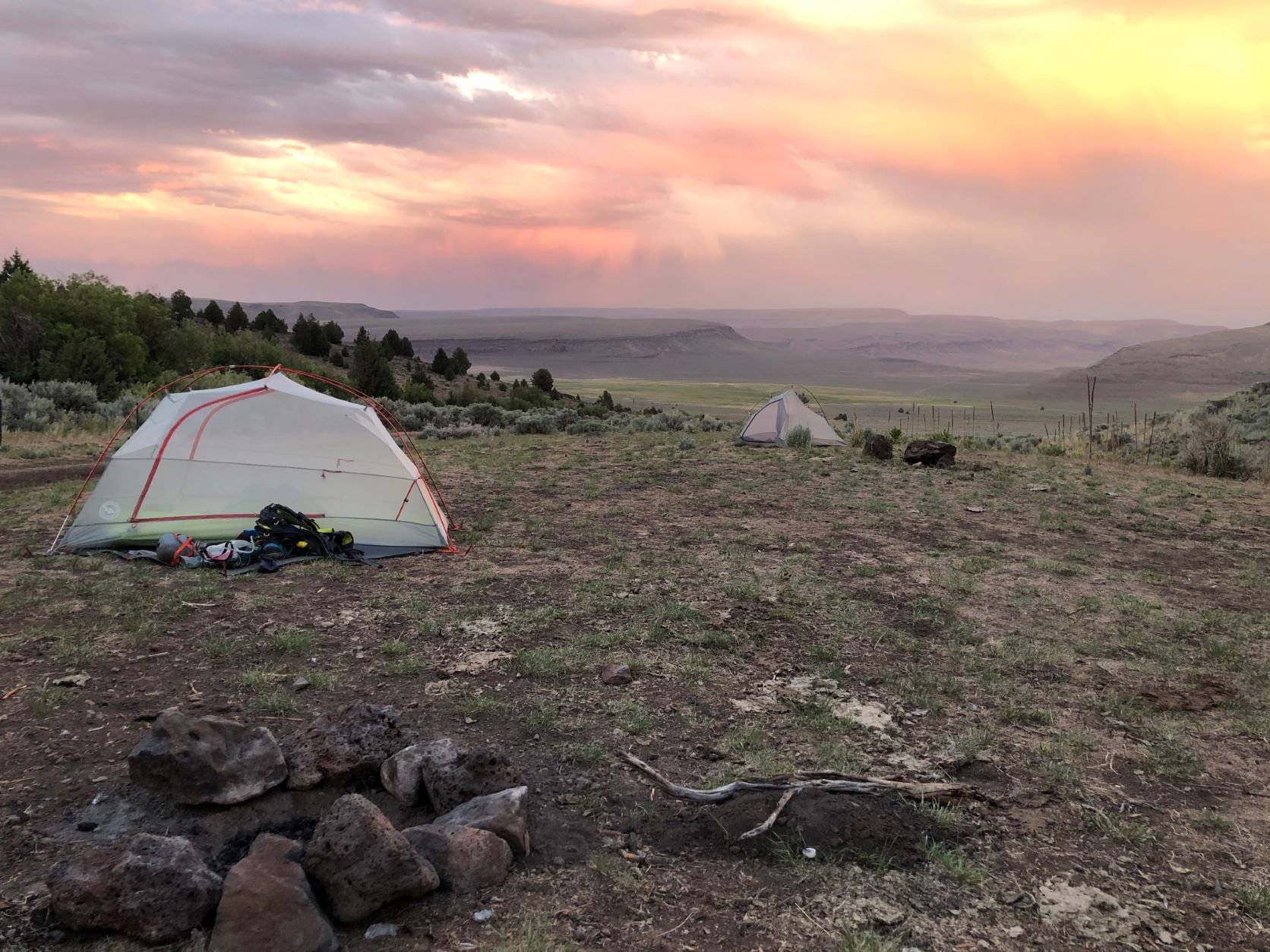 Tents in a canyon on the east of Steens Mountain, with a yellow, pink, and purple sunset in the background.