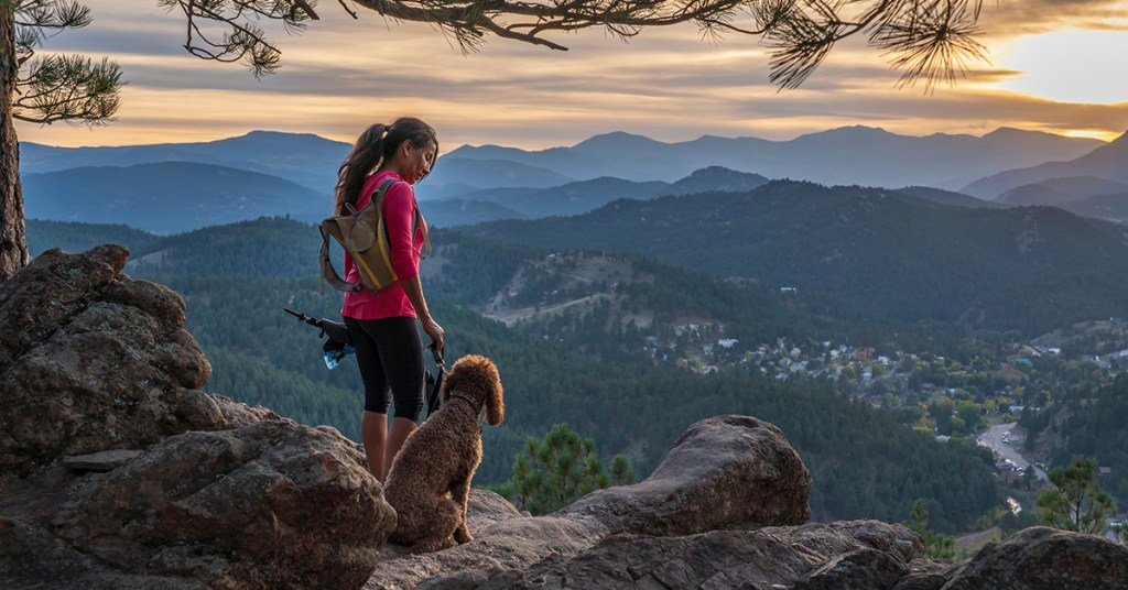 girl hiking with dogs