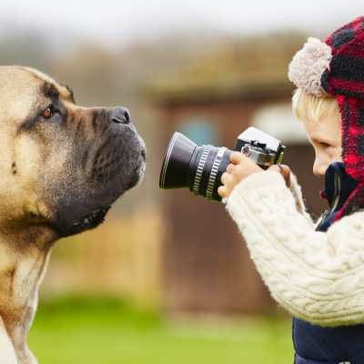 a little boy takes a picture of his dog