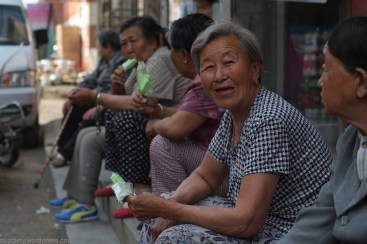 elderly Chinese women talking on a curb