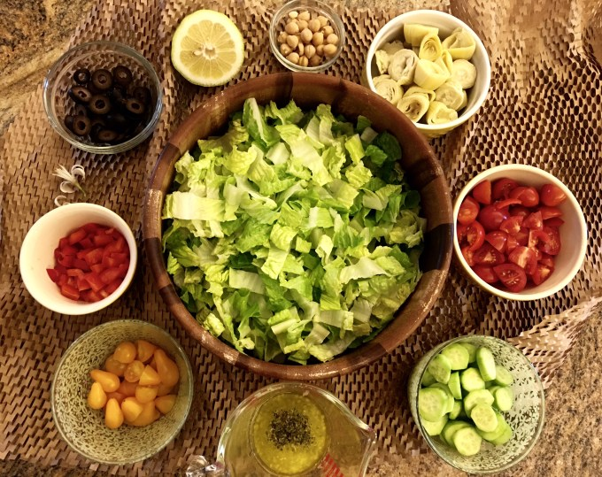 lettuce, tomatoes, cucumbers, olives, beans, red peppers, dressing, lemon, Greek salad