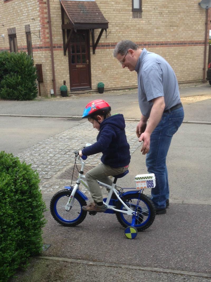 Pedalling his bike