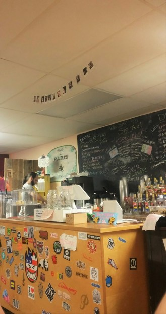 Sip's main counter decorated with local stickers. Their specials chalkboard gives the place a handmade feel.