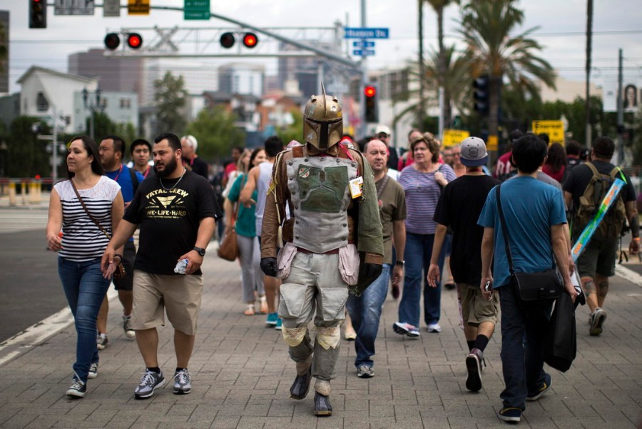A person wearing a costume to resemble the Star Wars character of Boba Fett crosses the street during the 2014 Comic-Con International Convention in San Diego