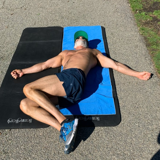 Athlete Dane Findley, age 53, demonstrates windshield wipers – a mobility maneuver to limber up the spine.