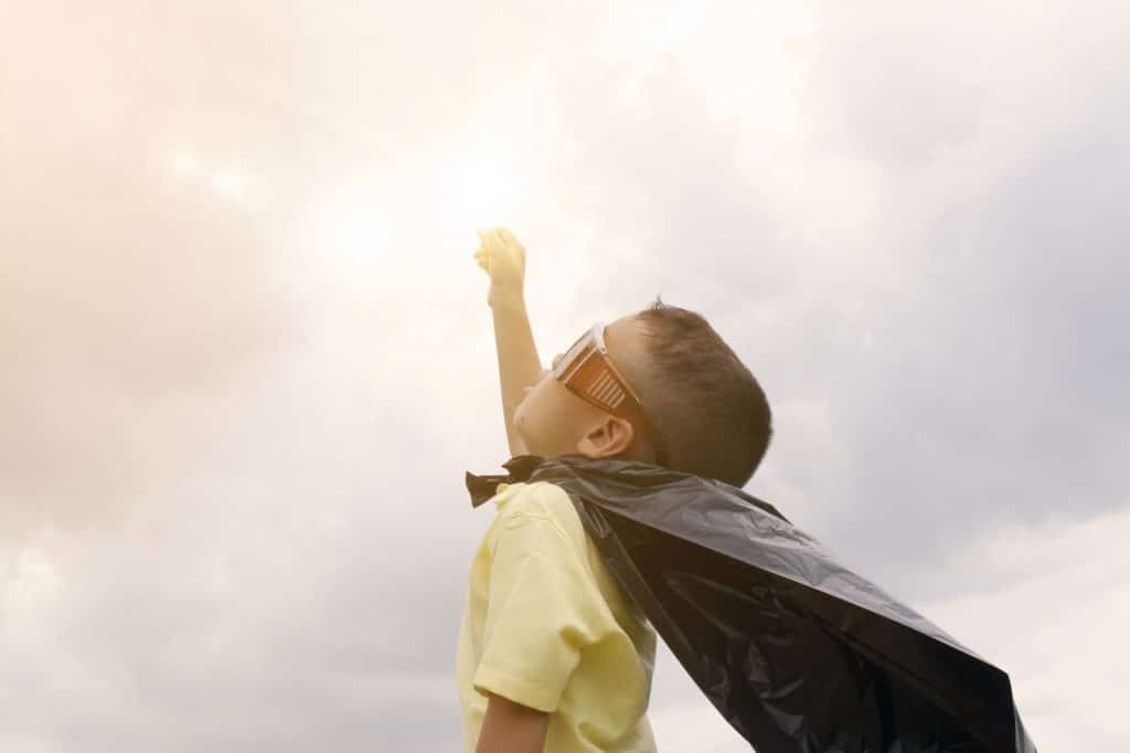 A child dressed as a superhero pointing towards the sun.