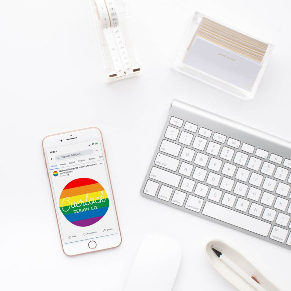 A photo of a desktop, with a keyboard, business cards, and an iPhone displaying my logo in the rainbow flag colors.