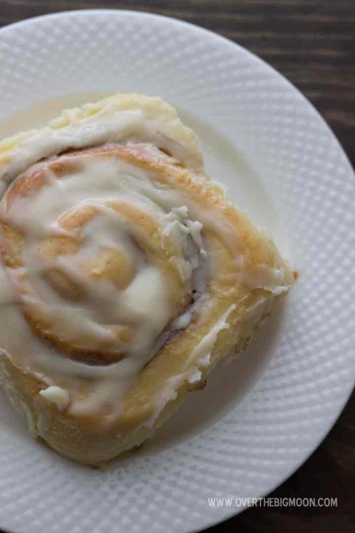 A cinnamon roll with frosting on a white plate!