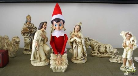 An Elf sitting by a white porcelain nativity.