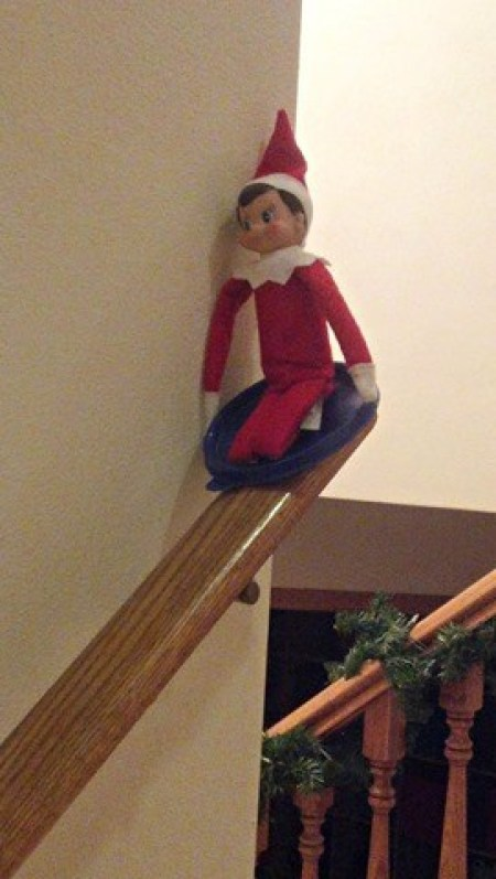 An Elf on a tupperware lid, sledding down a stair banister.