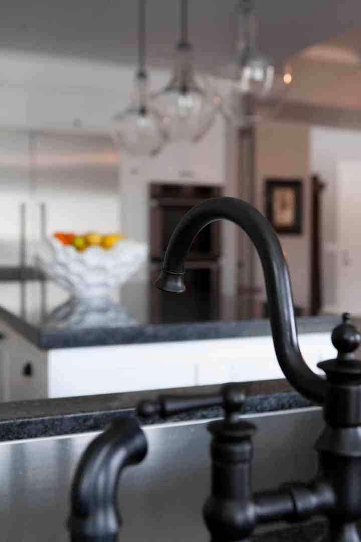 Black sink faucet, over a stainless steel sink. In the background you see a kitchen island with a white fruit bowl on the counter.