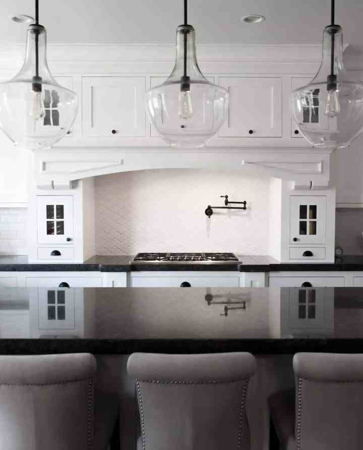 White kitchen with 3 clear glass large pendent lights hanging over a kitchen island with 3 chairs up to the counter.