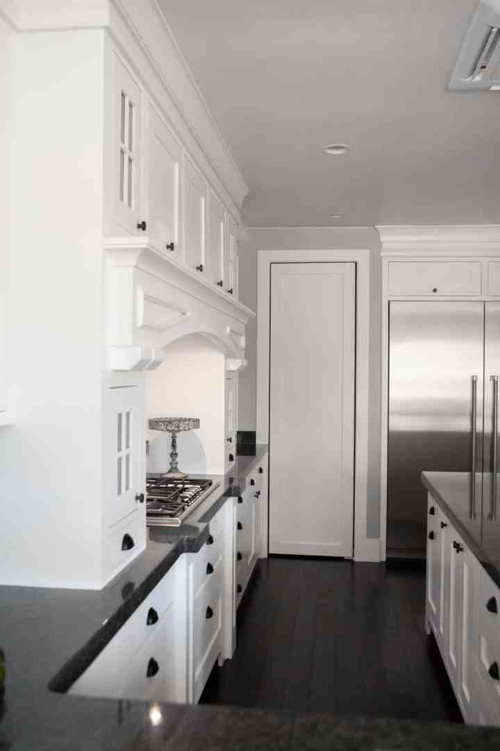 White kitchen with black countertops. At the center of the picture is a white tall skinny door.