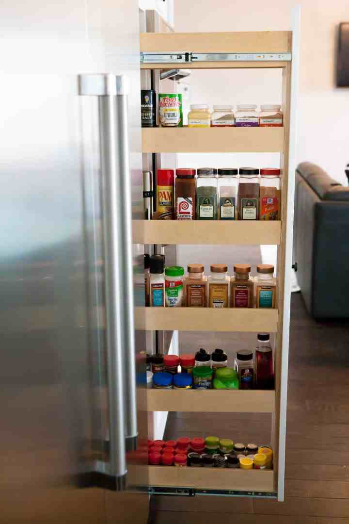 A rolling spice rack filled with spices.