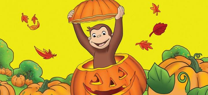 Curious George popping out of a carved pumpkin.