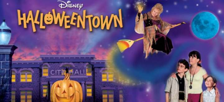 Halloweentown Movie Cover - a city in the background with 3 kids and her Grandma, the witch, on a broom in the air.