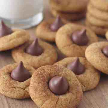 A bunch of Peanut Butter cookies with Hershey Kisses on them on top of a cutting board, with a glass of milk in the background.