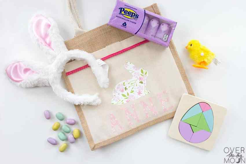 DIY Easter Bag for Kids -- this project is too fun with the patterned iron on vinyl and pom pom trim! From overthebigmoon.com!