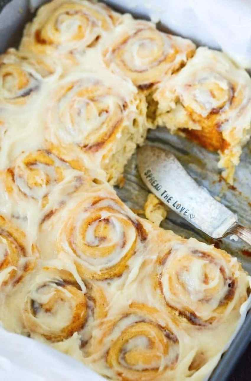 A pan of Pumpkin Cinnamon Rolls covered with icing. A spatula is laying where a few cinnamon rolls used to be.