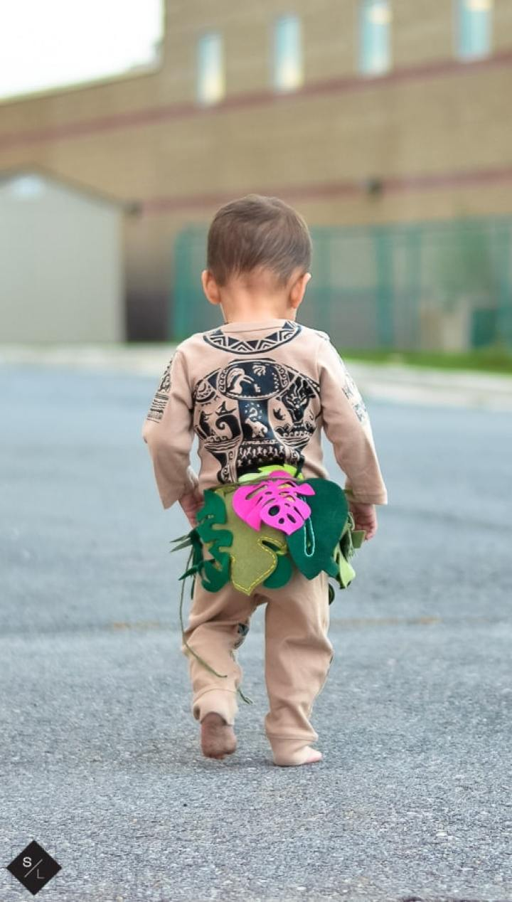 A ittle boy dressed up as Maui from Moana. Cute little leaf belt and onesie covered in Iron On tattoos.