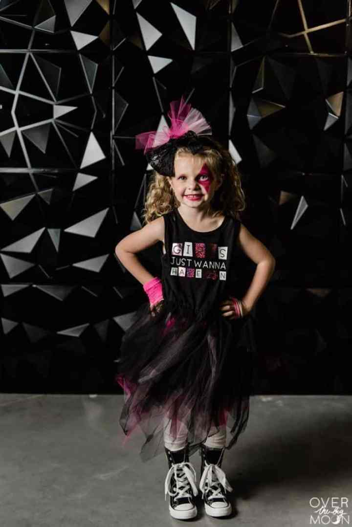 A little girl dressed up as a little Rock Star with a black dress, large pink bow and black high tops!