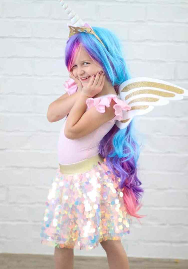 A little girl dressed up as a unicorn with long colorful hair, wings and a pink sparkly skirt on.
