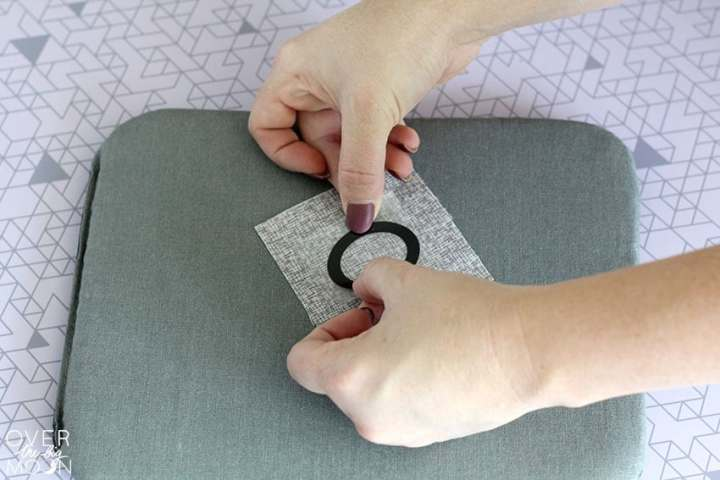 Apply X's and O's to a square of fabric.