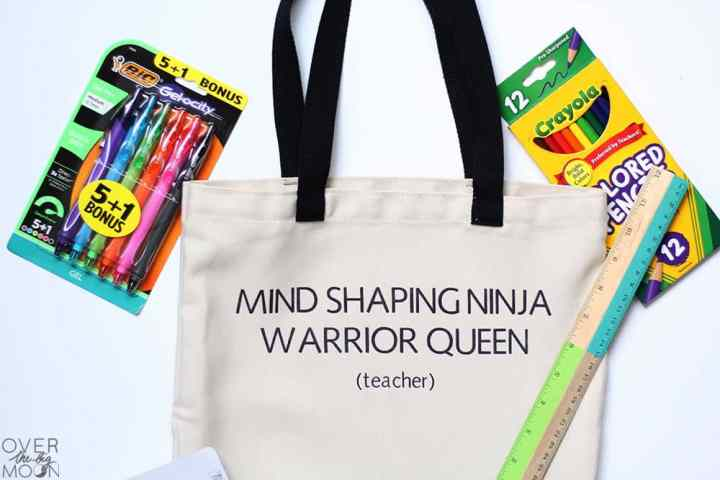 "A tote bag that says ""Mind Shaping Ninja Warrior Queen (Teacher),"" surrounded by school supplies."