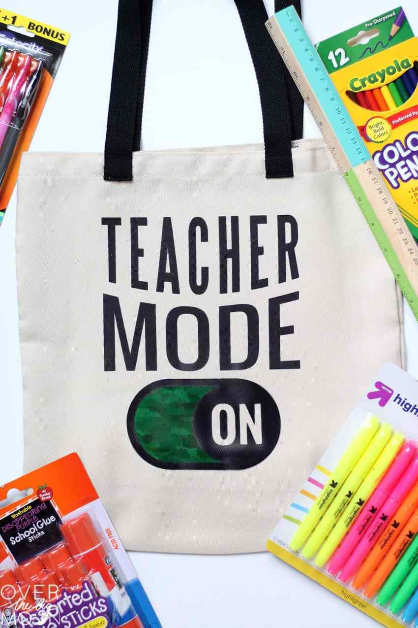 """Teacher Tote bag the says """"Teacher Mode On,"""" surrounded by school supplies."""