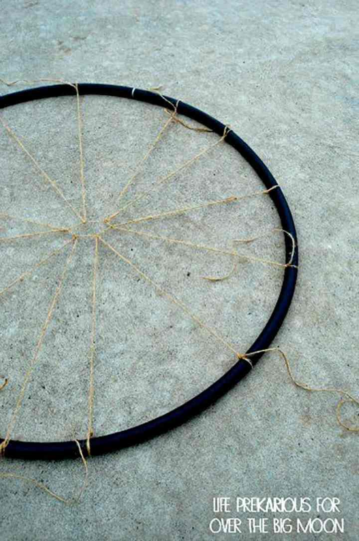 A Hula Hoop with Jute Twine being tied to a Hula Hoop to make a Spider Web.