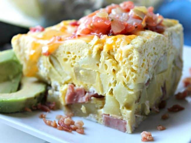 A pie wedge of Instant Pot Egg Casserole. The egg casserole is full of potatoes, cheese, ham and cheese. The wedge is topped with cheese and pico and has avocado slices on the side
