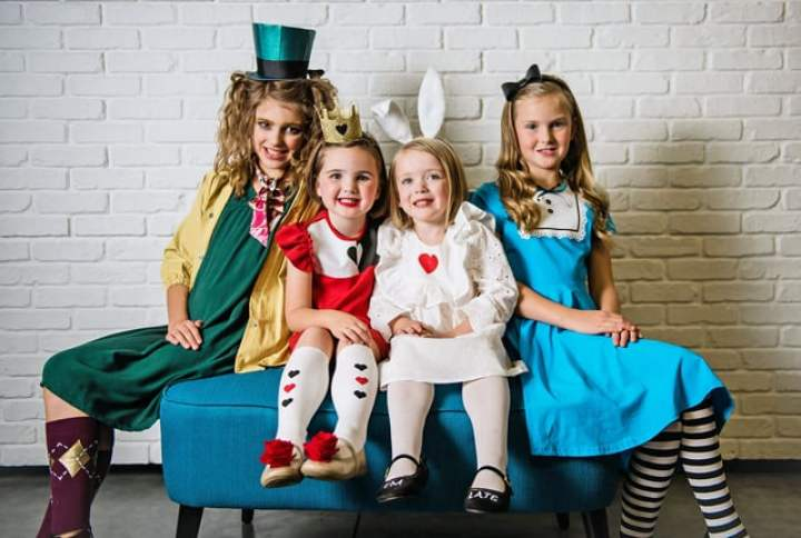 4 little girls dressed up as the Mad Hatter, Queen, Rabbit and Alice from Alice In Wonderland.