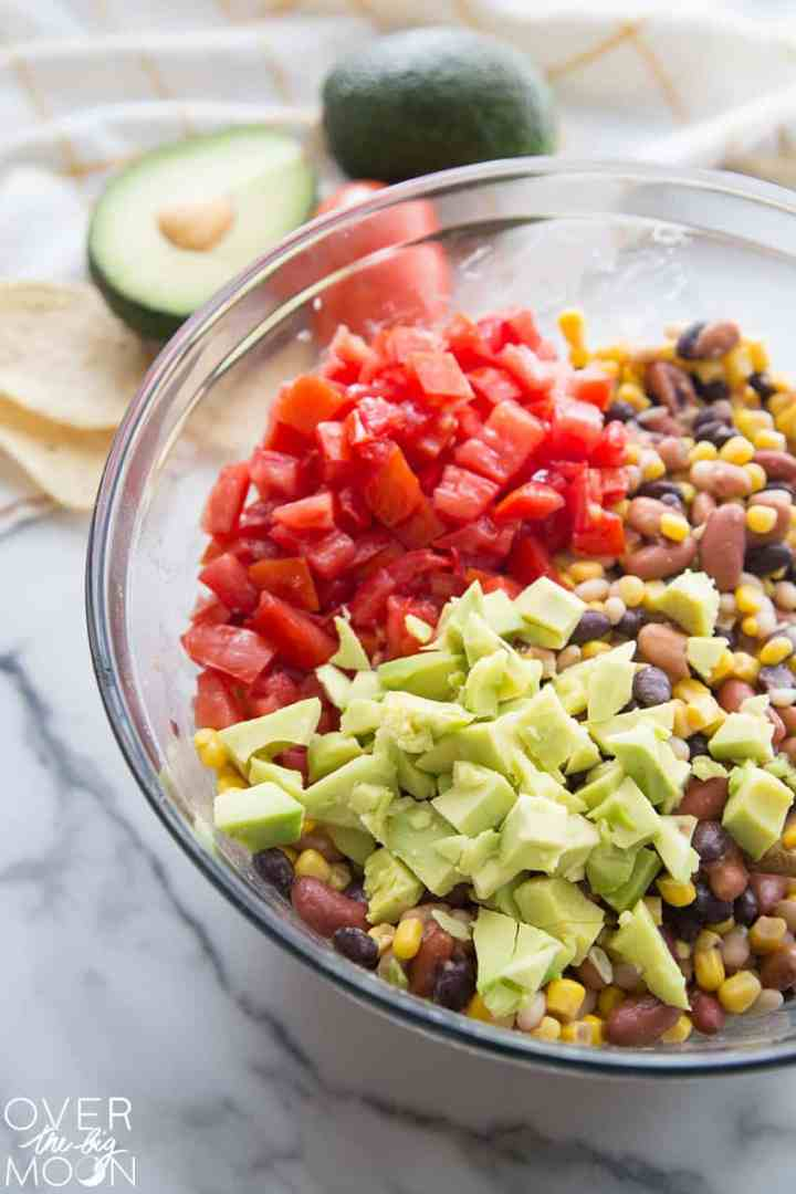 4 types of beans and corn mixed in a bowl with chopped tomato and avocado on top of it.