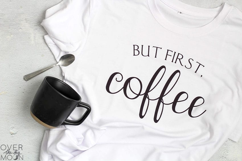 """A white shirt that says """"But first, coffee"""" on it. With a black coffee mug and spoon."""